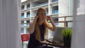 Mujer joven que se sienta en un balcón con un cuaderno y que sufre de un fuerte ruido producido por un emplazamiento de la obra c almacen de video
