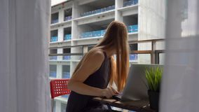 Mujer joven que se sienta en un balcón con un cuaderno y que sufre de un fuerte ruido producido por un emplazamiento de la obra c almacen de metraje de vídeo