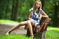 Mujer joven que se sienta en un banco Foto de archivo