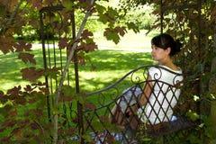 Mujer joven que se sienta en un banco Imagen de archivo