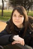 Mujer joven que se sienta en un banco fotos de archivo libres de regalías