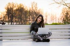 Mujer joven que se sienta en un banco, cerca de la universidad, trabajando con el ordenador portátil Fotografía de archivo libre de regalías