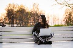 Mujer joven que se sienta en un banco, cerca de la universidad, trabajando con el ordenador portátil Imagenes de archivo