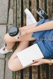 Mujer joven que se sienta en un banco con la taza de café Imagen de archivo libre de regalías