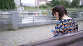 Mujer joven que se sienta en un banco en el parque y que escucha la música foto de archivo libre de regalías