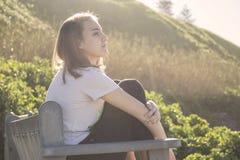 Mujer joven que se sienta en un banco en la playa que mira en el aire fotos de archivo libres de regalías