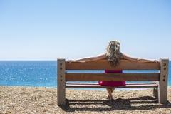 Mujer joven que se sienta en un banco y que mira el mar fotos de archivo