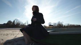 Mujer joven que se sienta en un barco en la playa en tiempo soleado en el baile y el relleno del mar B?ltico tontos almacen de video
