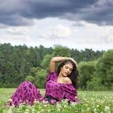 Mujer joven que se sienta en un césped verde Fotos de archivo libres de regalías