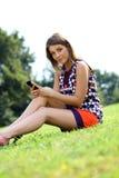 Mujer joven que se sienta en un césped verde Imágenes de archivo libres de regalías