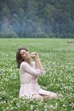 Mujer joven que se sienta en un césped verde Imagen de archivo
