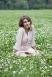 Mujer joven que se sienta en un césped verde Fotos de archivo
