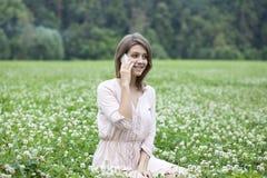 Mujer joven que se sienta en un césped verde Fotografía de archivo