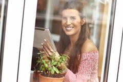 Mujer joven que se sienta en un café Fotografía de archivo libre de regalías