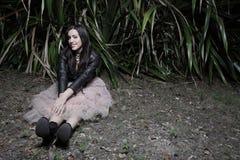 Mujer joven que se sienta en un campo oscuro Fotos de archivo