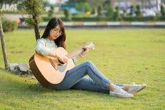 Mujer joven que se sienta en un campo y que toca la guitarra Imagenes de archivo