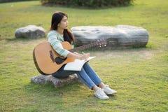 Mujer joven que se sienta en un campo y que toca la guitarra Imagen de archivo