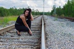 Mujer joven que se sienta en un ferrocarril Foto de archivo libre de regalías