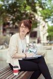 Mujer joven que se sienta en un funcionamiento del banco de parque Foto de archivo
