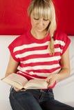 Mujer joven que se sienta en un libro de lectura del sofá Imágenes de archivo libres de regalías