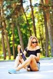 Mujer joven que se sienta en un monopatín - al aire libre Fotos de archivo libres de regalías