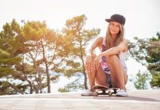 Mujer joven que se sienta en un monopatín al aire libre Fotos de archivo