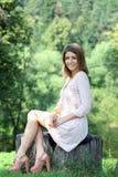mujer joven que se sienta en un parque del verano Imagen de archivo libre de regalías