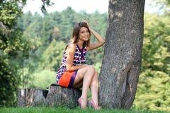 mujer joven que se sienta en un parque del verano Imágenes de archivo libres de regalías