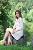 Mujer joven que se sienta en un parque del verano Fotografía de archivo libre de regalías