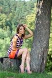 mujer joven que se sienta en un parque del verano Fotografía de archivo