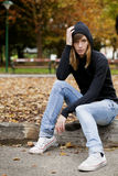 Mujer joven que se sienta en un parque en otoño Imagen de archivo