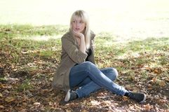 Mujer joven que se sienta en un prado Imagen de archivo