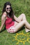 Mujer joven que se sienta en un prado cerca de las flores amarillas en una forma del sol Imágenes de archivo libres de regalías