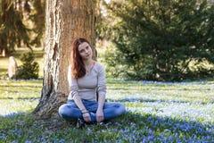 Mujer joven que se sienta en un prado de la flor Fotos de archivo libres de regalías
