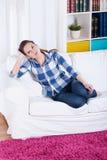 Mujer joven que se sienta en un sofá fotografía de archivo libre de regalías