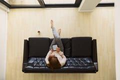 Mujer joven que se sienta en un sofá con la tableta digital que practica surf en línea Foto de archivo