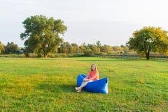 Mujer joven que se sienta en un sofá del aire contra la perspectiva de prado verde Fotos de archivo