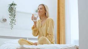 Mujer joven que se sienta en una cama y un agua potable almacen de video