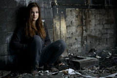 Mujer joven que se sienta en una casa quemada Imágenes de archivo libres de regalías