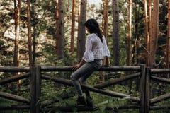 Mujer joven que se sienta en una cerca de madera en el bosque entre árboles de pino foto de archivo libre de regalías