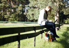 Mujer joven que se sienta en una cerca rústica Imagen de archivo libre de regalías