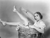 Mujer joven que se sienta en una cesta que parece sorprendida (todas las personas representadas no son vivas más largo y ningún e imagenes de archivo