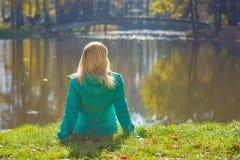 Mujer joven que se sienta en una hierba cerca del lago Foto de archivo libre de regalías