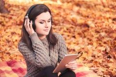 Mujer joven que se sienta en una manta y que escucha la música fotos de archivo libres de regalías