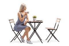 Mujer joven que se sienta en una mesa de centro fotos de archivo libres de regalías