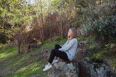 Mujer joven que se sienta en una piedra grande Imagen de archivo
