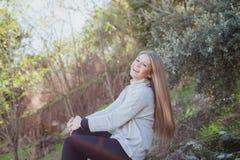 Mujer joven que se sienta en una piedra grande Foto de archivo libre de regalías