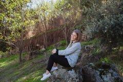Mujer joven que se sienta en una piedra grande Fotografía de archivo libre de regalías