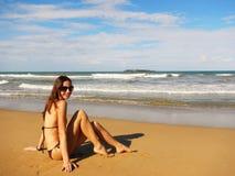 Mujer joven que se sienta en una playa, EL Limon de Playa Fotografía de archivo