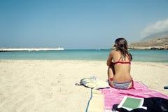 Mujer joven que se sienta en una playa hermosa Imágenes de archivo libres de regalías